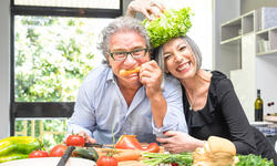 Senior couple having fun in kitchen with healthy f